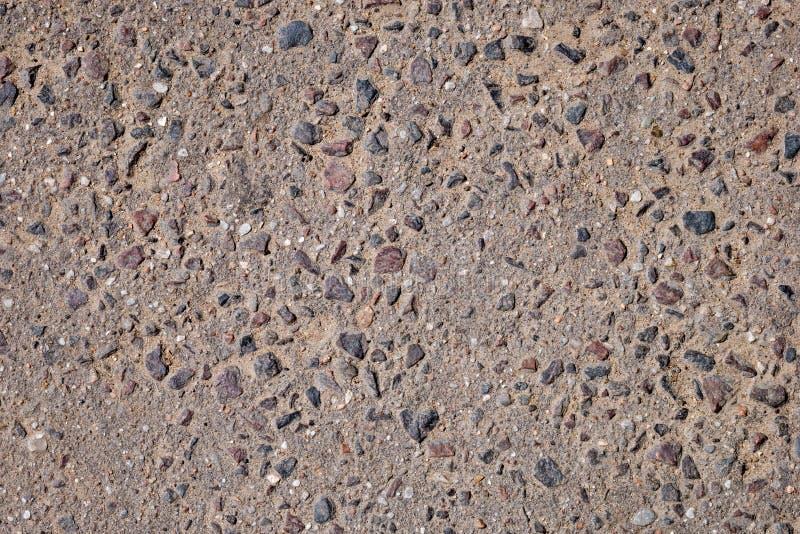 Brun asfalt med kulöra stenar royaltyfria foton