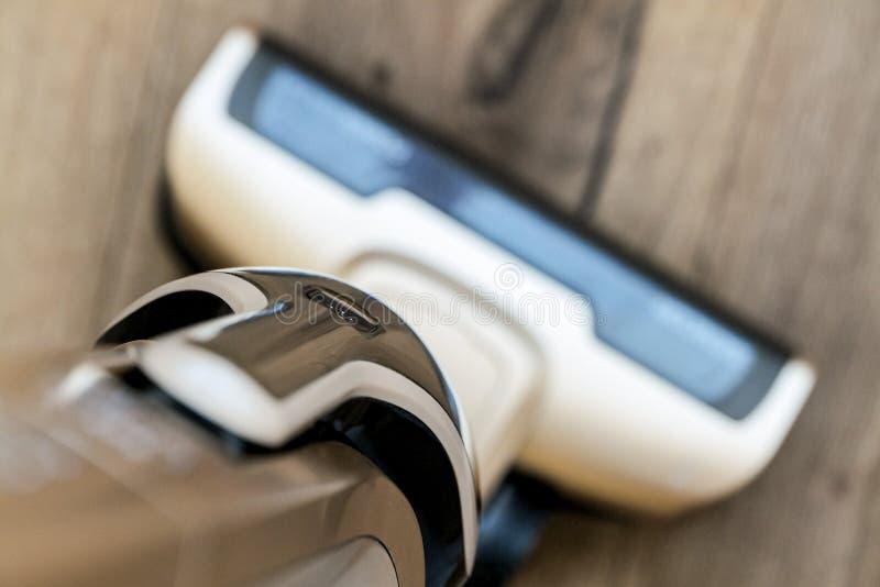 Brun bärbar sladdlös dammsugare på ett trägolv för att göra ren ett hushåll arkivbilder