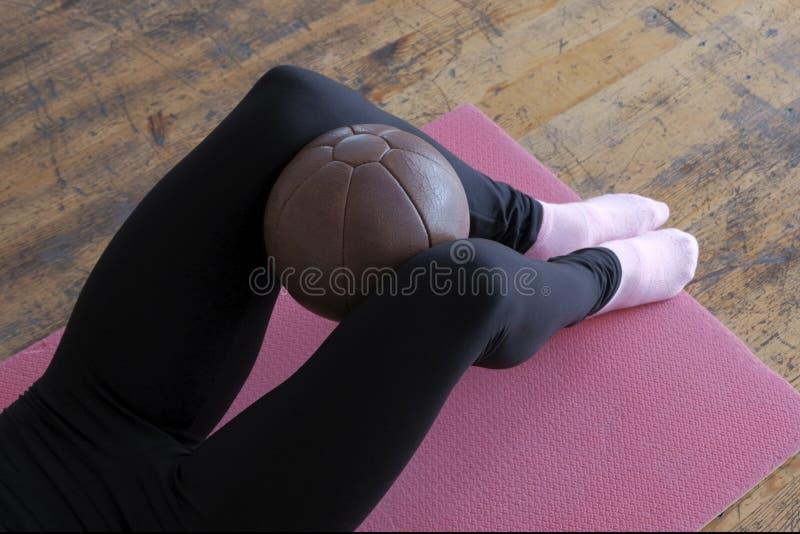 Brun boll som klämmas fast mellan knä Konditionövning Kvinnliga ben i svarta flåsanden på ett rosa gymnastiskt mattt arkivfoton