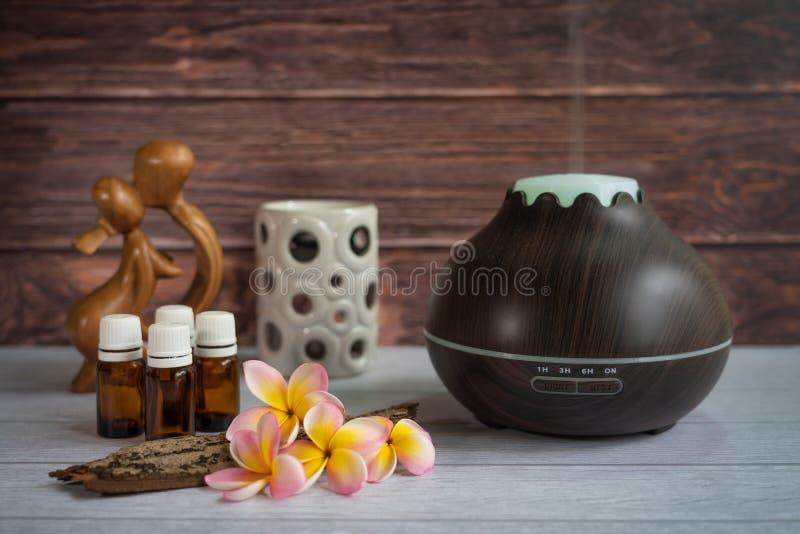 Brun diffusor för nödvändig olja med frangipaniblommor, stearinljuset och den lilla träförälskelsestatyn fotografering för bildbyråer