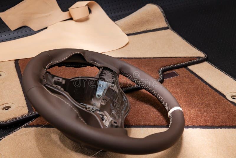 Brun färg för läderstyrninghjul i processen av att sy med en ljus kontrastsöm och vit central punkt på överkanten in arkivfoton