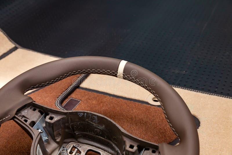 Brun färg för läderstyrninghjul i processen av att sy med en ljus kontrastsöm och vit central punkt på överkanten in royaltyfri bild