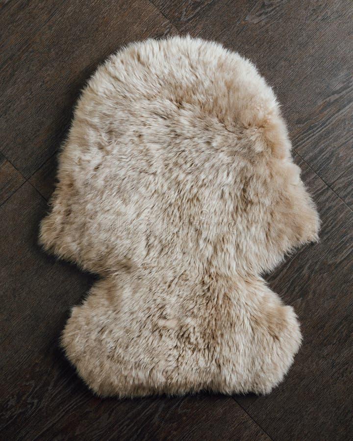 Brun fårskinnpälsmatta på träbakgrund arkivfoton