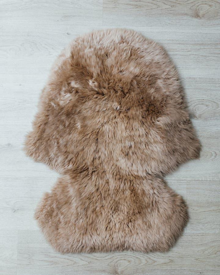 Brun fårskinnpälsmatta på trägolv royaltyfri bild