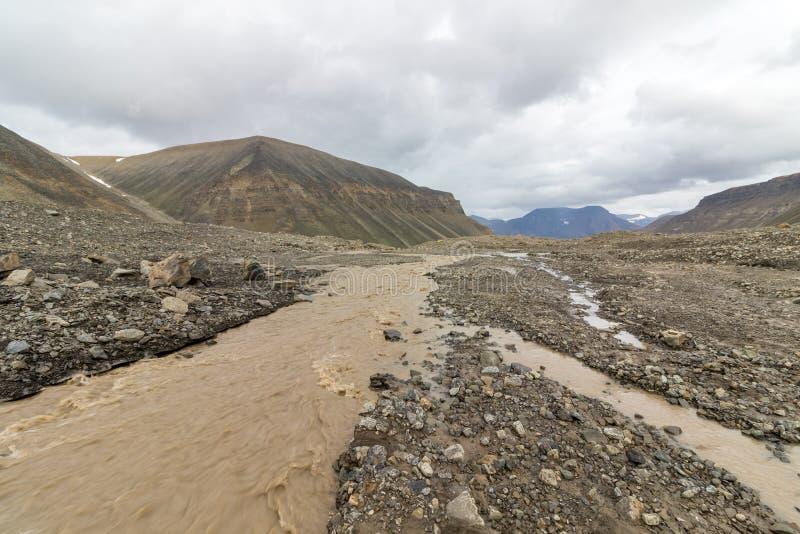 Brun flod med smältande vatten från den Longyear glaciären som kör till och med den Longyear dalen Arktiskt landskap av arkivbilder