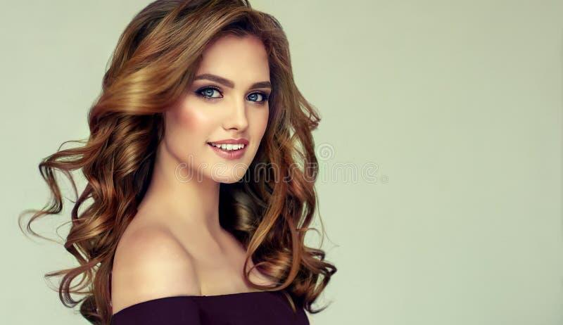 Brun haired kvinna med den omfångsrika, skinande och lockiga frisyren Burrigt hår