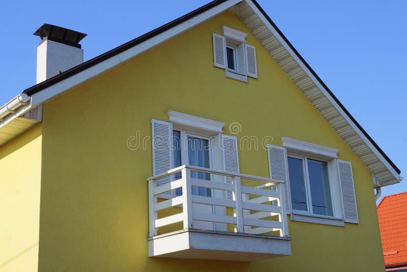Brun husfasad med fönster och en vit träbalkong mot himlen fotografering för bildbyråer