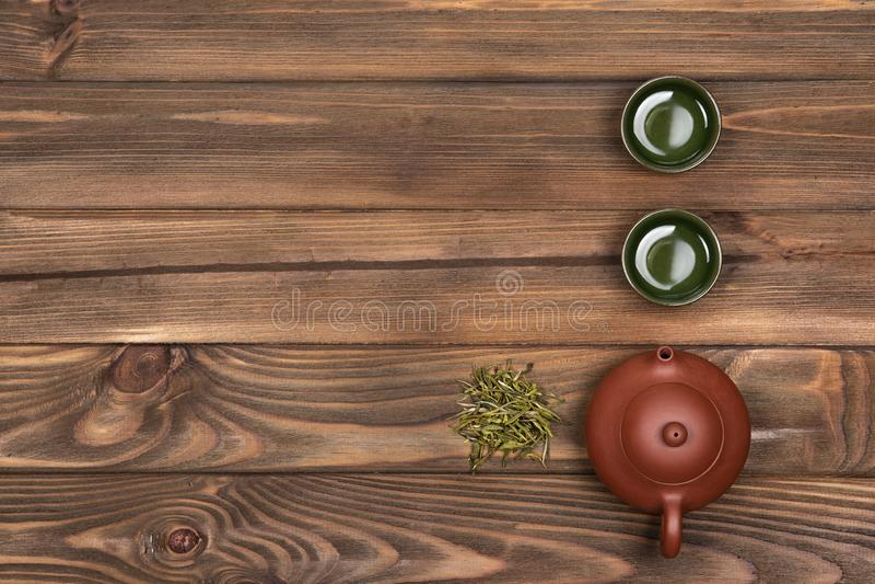 Brun keramisk tekanna, mörka två - gröna speciala koppar och grönt te på en mörk träplanked bakgrund Grön tea med koppen och teap arkivbilder