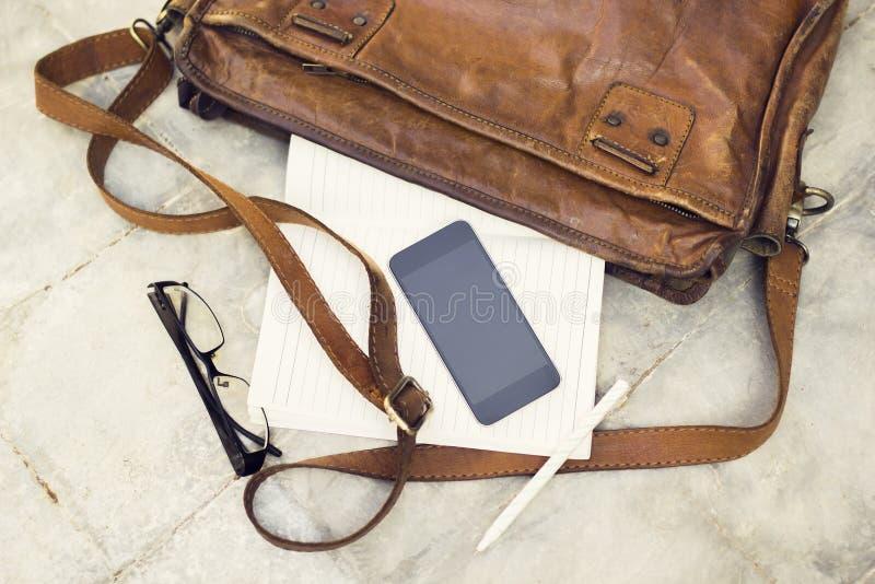 Brun läderhandväska, tom mobiltelefon, dagbok och exponeringsglas arkivfoto