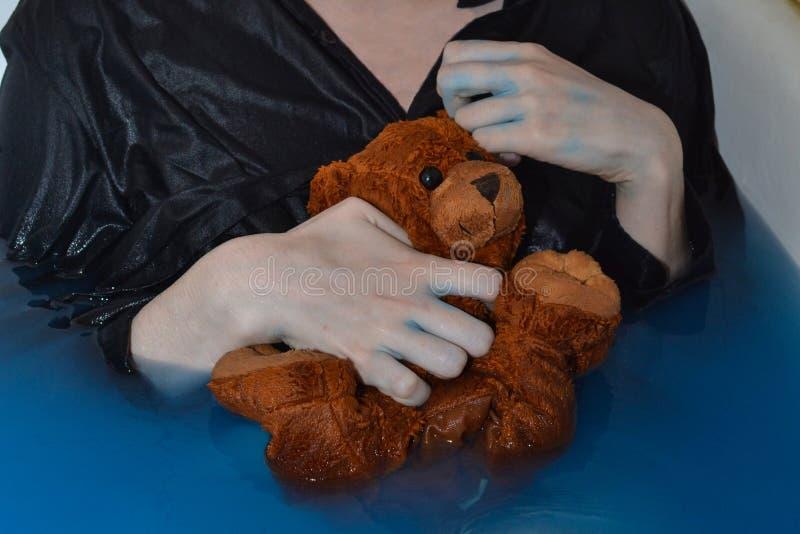 Brun liten våt björn i händerna royaltyfria foton