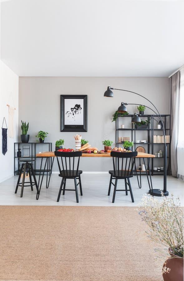 Brun matta och affisch i grå matsal som är inre med lampan bredvid stolar och tabellen fotografering för bildbyråer