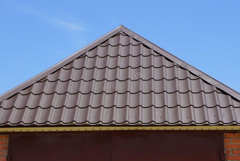 Brun metalltegelplatta på taket av ett hus fotografering för bildbyråer