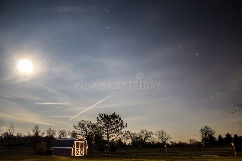 Brun och vit ladugård och gräsplan Tress Under Blue Sky under dag arkivbilder