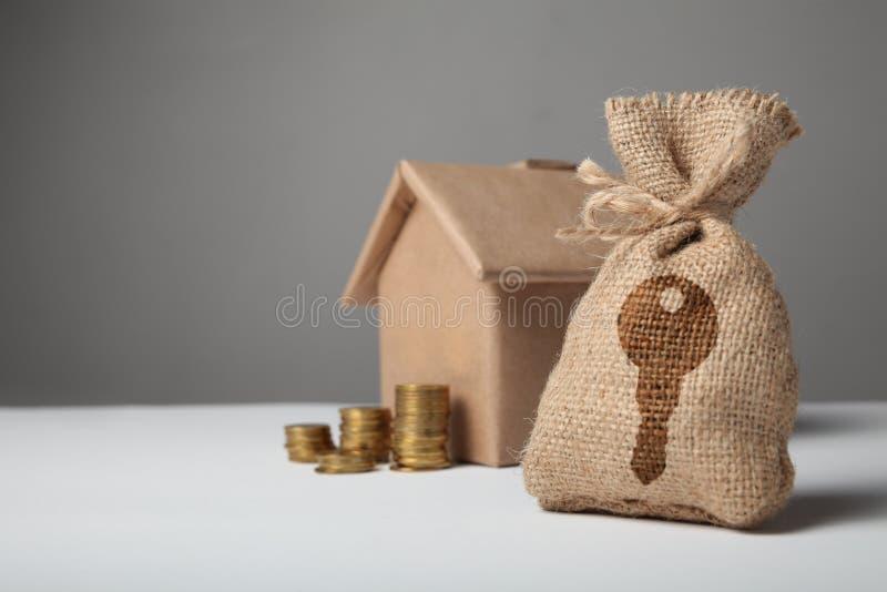 Brun påse med nyckel- logo Guld- mynt och hem- pappers- hus Begreppet av det hyra och köpande huset royaltyfri foto