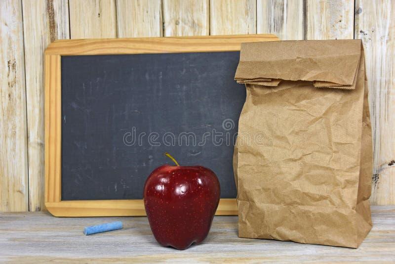 Brun pappers- påse med det röda äpplet och den svart tavlan fotografering för bildbyråer