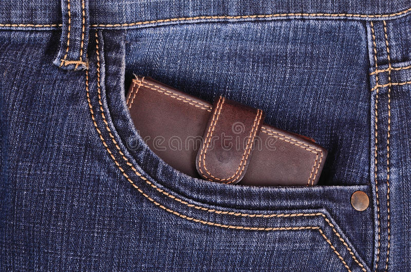 Brun plånbok i jeansfacket arkivfoto