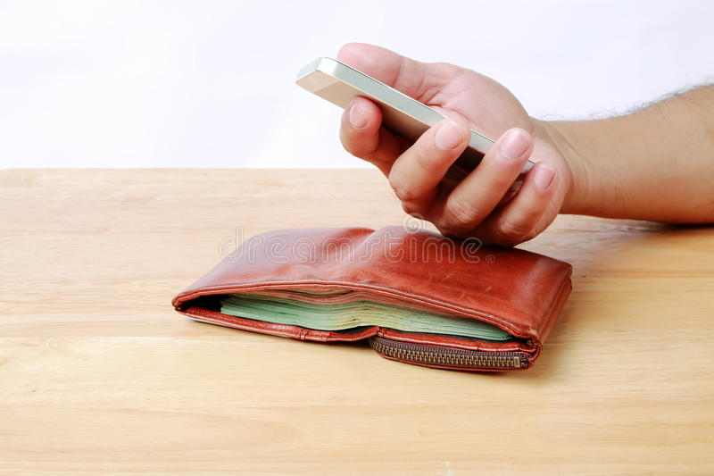 Brun plånbok och mobiltelefon i hand på wood bakgrund arkivbilder