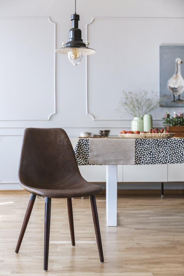 Brun stol under lampan i den vita matsalinre med tabellen och väggen med stöpningen Verkligt foto royaltyfria foton