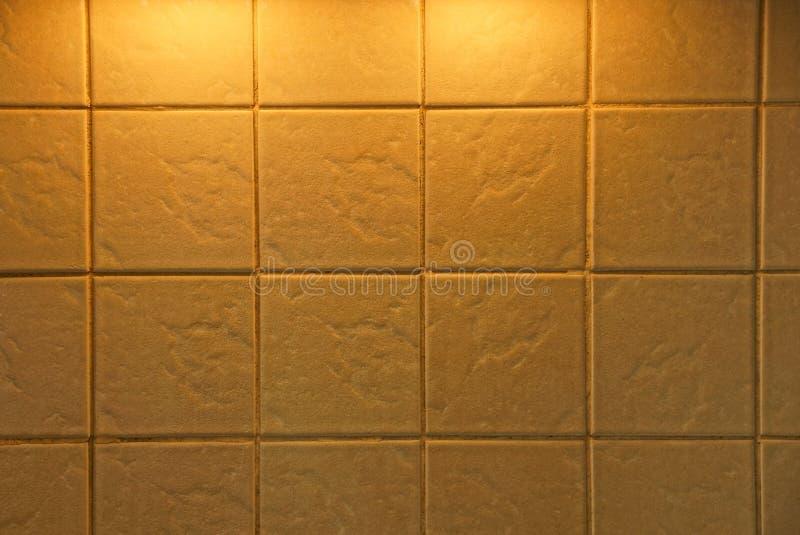 Brun textur av en fyrkantig tegelplatta på en vägg i ett rum arkivbilder