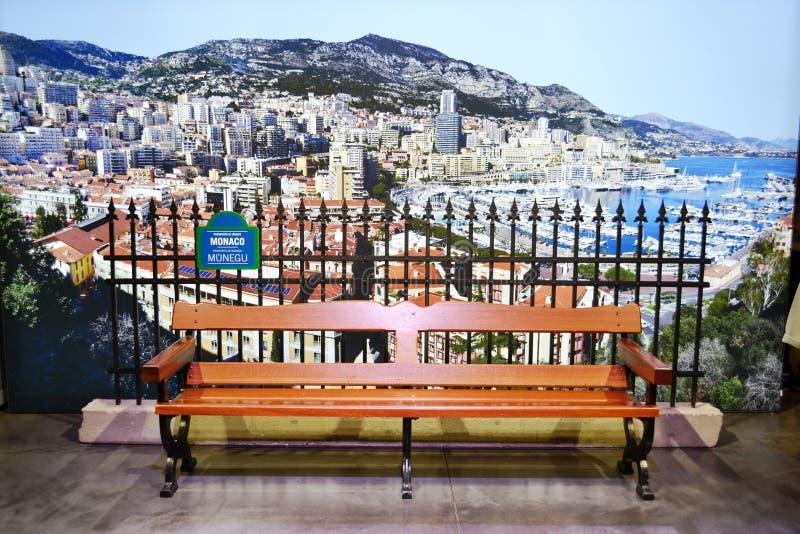 Brun träbänk och ett stort panorama- stadsfoto på den Monaco paviljongen av EXPON Milano 2015 royaltyfria foton
