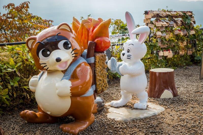 Brun tvättbjörn och vit kaninstaty på den Kachi Kachi ropewaysynvinkeln, Japan royaltyfria foton
