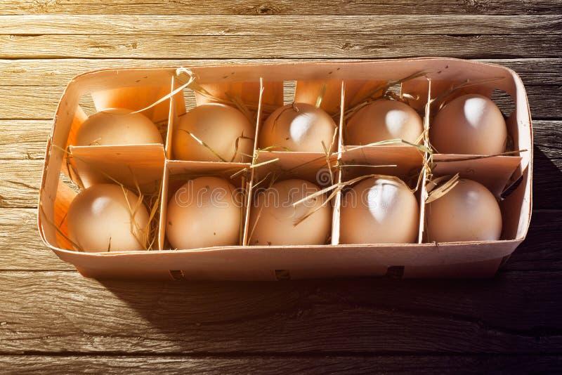 Bruna ägg i träbunke på wood bakgrund arkivfoto