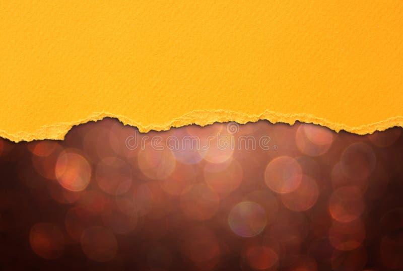 Bruna bokehljus och orange sönderrivet papper arkivbild