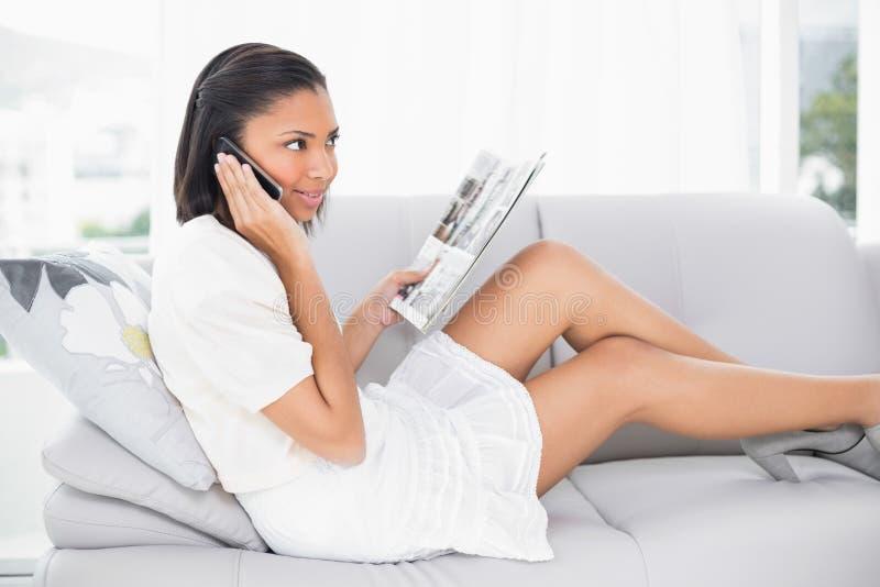 Bruna giovane di pensiero in vestiti bianchi che fanno una telefonata immagini stock