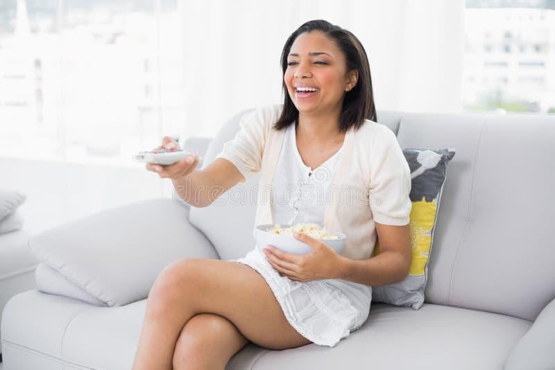 Bruna giovane di risata in televisione di sorveglianza dei capelli bianchi immagine stock libera da diritti