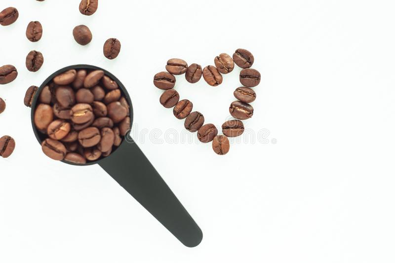 Bruna grillade kaffebönor i en svart mäta sked på en isolerad vit bakgrund royaltyfri bild