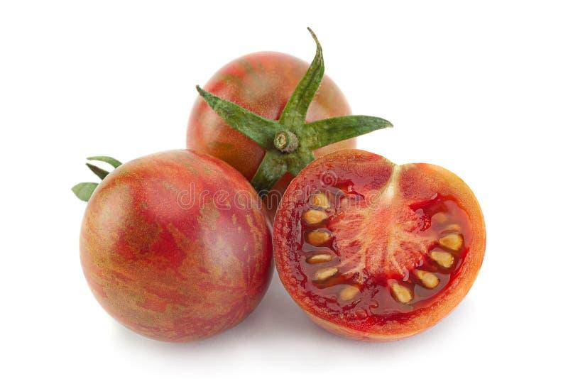 Bruna körsbärsröda tomater på vit royaltyfria bilder