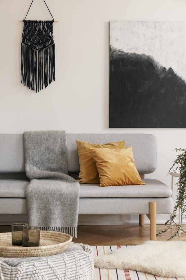 Bruna kuddar och filt på den gråa soffan i naturlig uppehälle Verkligt foto royaltyfri fotografi