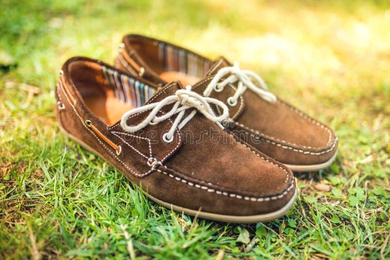 Bruna lädermäns skor, eleganta sommarmockasin i gräs Män danar, mantillbehör och skodon arkivfoto