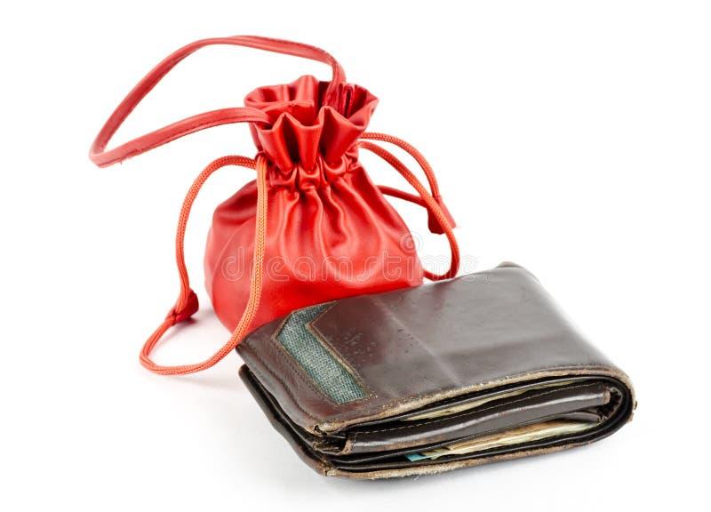 Bruna mäns plånbok med kvinnors röda handväska fotografering för bildbyråer