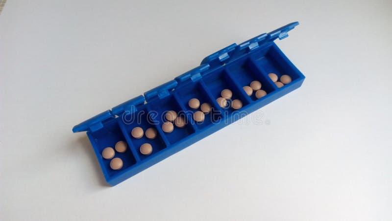 Bruna medicinska minnestavlor i blå ask för dosering på en vit bakgrund arkivbilder