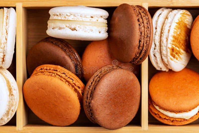 Bruna och vita franska macarons eller makron som staplas i tre rum, boxas royaltyfri bild