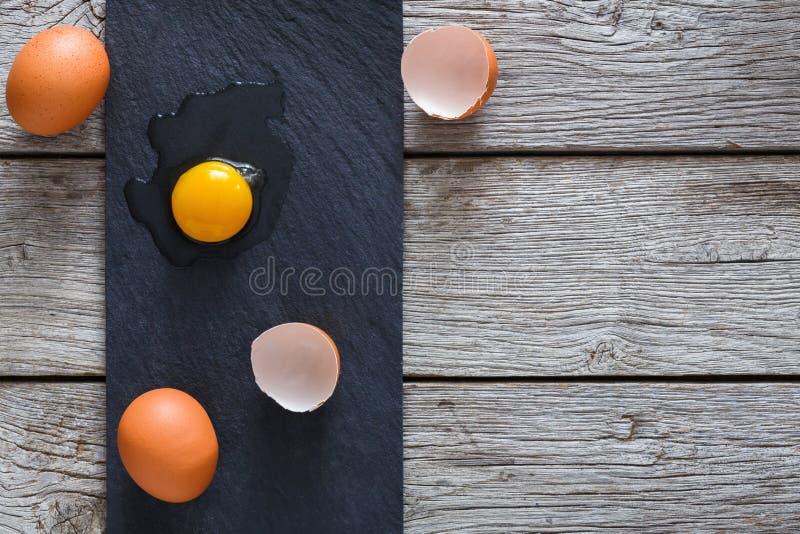 Bruna organiska spruckna ägg med äggula på svart wood bakgrund royaltyfria foton