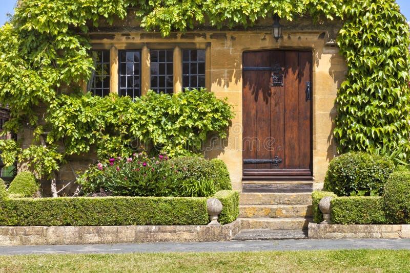 Bruna trädörrar till den traditionella engelska asfulla stugan, trädgård royaltyfri fotografi