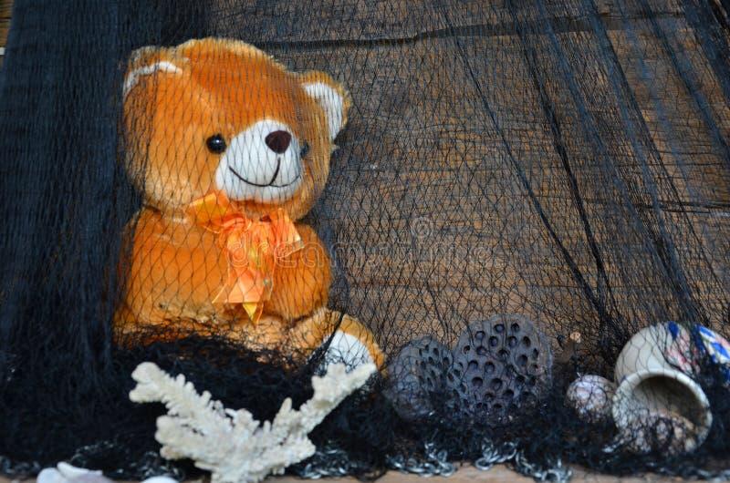 Brunbjörndocka och saker i svart ingrepp royaltyfri bild
