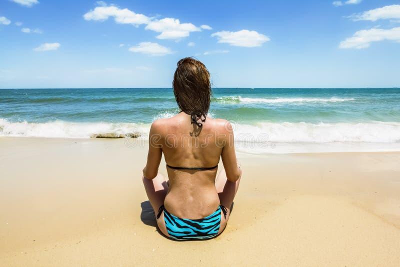 Brunbränd flicka i bikinisammanträde på stranden royaltyfria foton