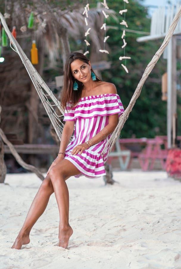 Brunbränd flicka som poserar att sitta i en hängmatta på vit sand arkivbild