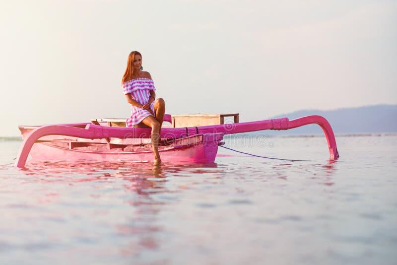 Brunbränd flickasimning på ett rosa fartyg royaltyfri foto