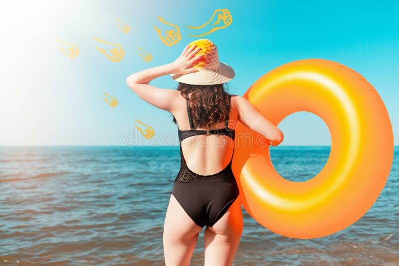 Brunbränd ung kvinna som rymmer en orange uppblåsbar cirkel och rymmer hennes huvud Havet i bakgrunden Begreppet av sommar royaltyfria bilder