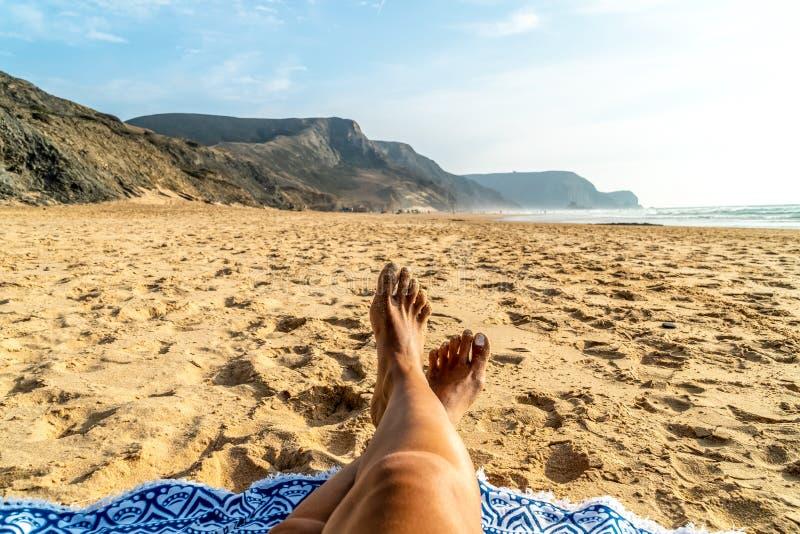 Brunbrända ben av kvinnan på stranden royaltyfri foto