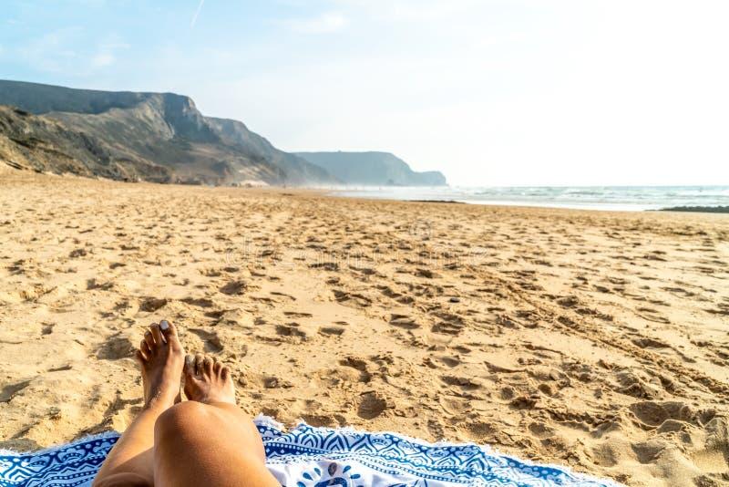 Brunbrända ben av kvinnan på stranden royaltyfri fotografi