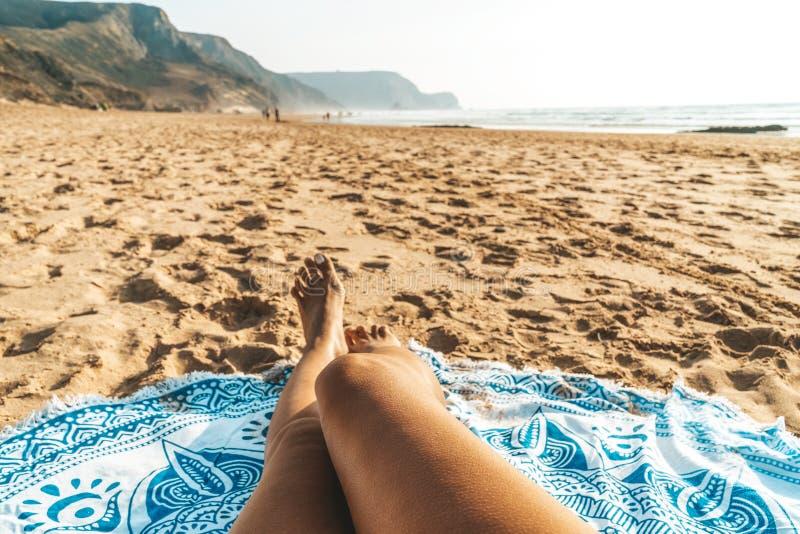 Brunbrända ben av kvinnan på stranden royaltyfria foton