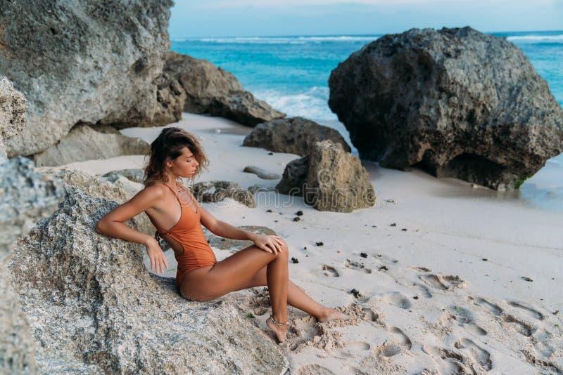 Brunbr?nd europeisk flicka f?r sidosikt i baddr?kten som sitter p? den steniga stranden av havet royaltyfri foto