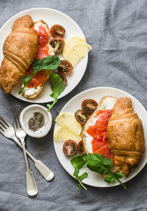 Brunch or breakfast table - croissants with cream cheese and smoked salmon, and cherry tomatoes. Delicious balanced breakfast, br. Unch or snack on a grey stock photography