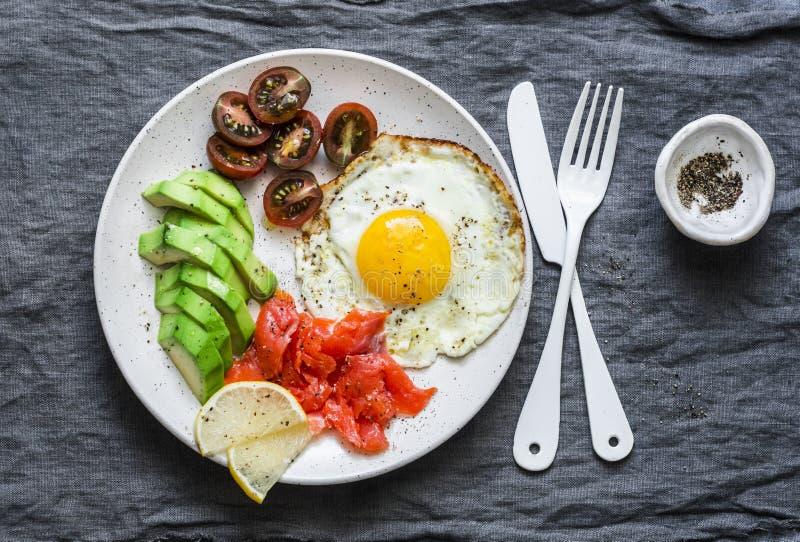 Brunch delicioso - huevo frito, aguacate, tomates de cereza y salmón ahumado en fondo gris imágenes de archivo libres de regalías