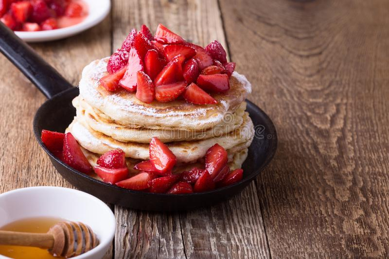 Strawberry  pancakes,  summer brunch rural table. Brunch, favorite morning meal. Homemade berry  pancakes, fresh summer dessert with strawberries, honey and royalty free stock images
